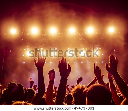 silhouettes of concert crowd in front of bright stage lights #494737801