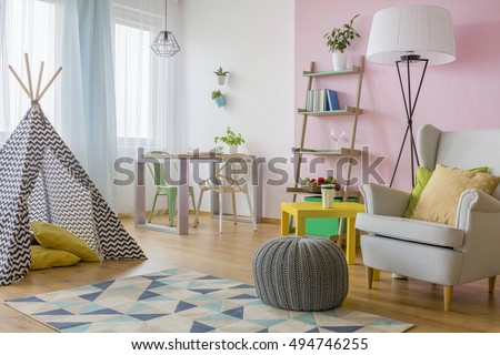 Spacious interior in pink and white with play tent, armchair, pouf, two chairs and table #494746255