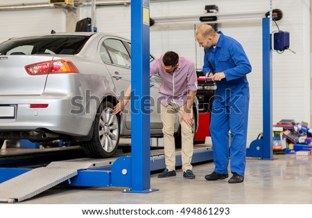 auto service, repair, maintenance and people concept - mechanic with clipboard and man or owner showing wheel at car shop #494861293