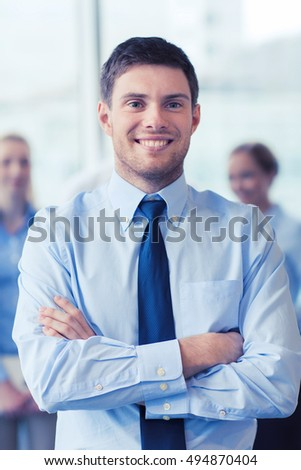 business, people and teamwork concept - smiling businessman with group of businesspeople in office #494870404
