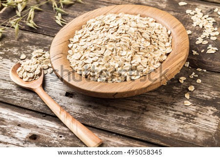Organic oat flakes on a wooden plate. #495058345