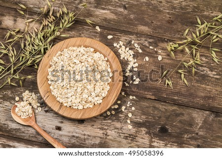 Organic oat flakes on a wooden plate. #495058396