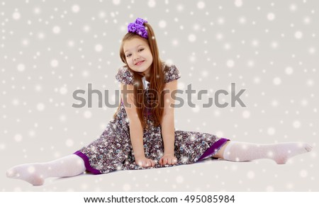Caucasian little girl with a big purple bow on her head. Girl shows how to do the splits.On the Christmas background with white snowflakes. #495085984