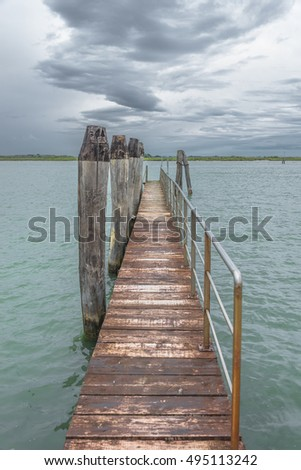 Wooden old pier at Burano, an island nearby Venice, Italy, summer time #495113242