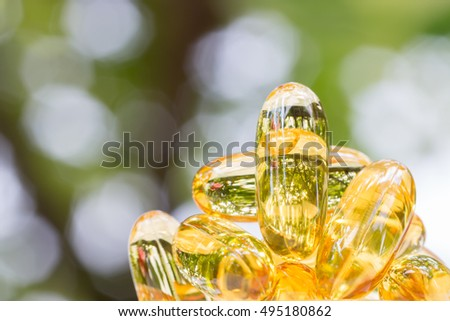 Macro image, pile of fish oil capsules on natural green blurred background. #495180862