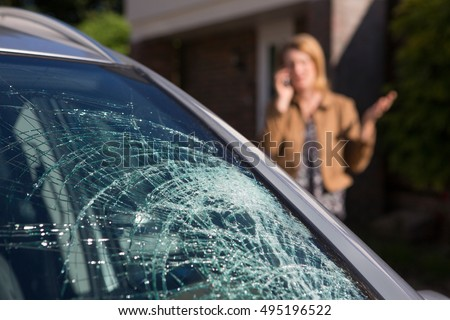 Woman Phoning For Help After Car Windshield Has Broken Royalty-Free Stock Photo #495196522