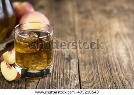 Peach ice tea (selective focus) on an old wooden table (close-up shot) #495210643