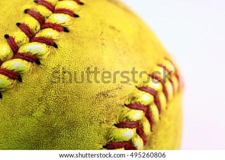 Yellow softball closeup with red seams.