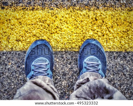 Top view of sneakers from above, male feet in casual footwear standing at dividing frontier line. #495323332