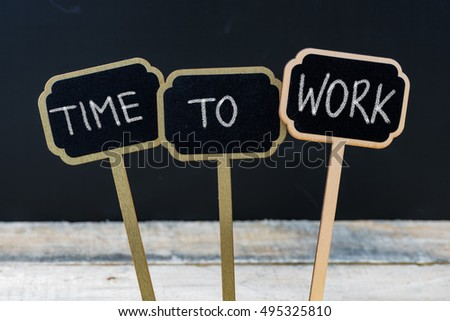 Business message TIME TO WORK written with chalk on wooden mini blackboard labels, defocused chalkboard and wood table in background #495325810