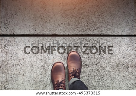 Comfort Zone Concept, Male with Leather Shoes Steps over a word with line on Concrete Floor, Top view #495370315