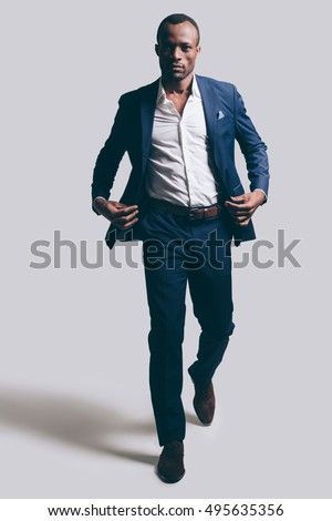 Confidence in every move. Full length of handsome young African man in full suit adjsuting his jacket while walking ahead and being in front of grey background Royalty-Free Stock Photo #495635356