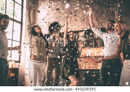 Confetti fun. Group of happy young people throwing confetti and jumping while enjoying home party on the kitchen  Royalty-Free Stock Photo #495639391