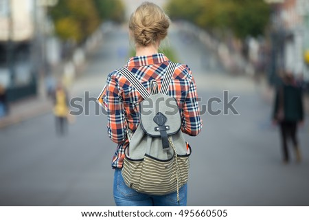 Young student girl walking down the street with a backpack, in the middle of the roadway. Back to school concept photo, back view, horizontal #495660505