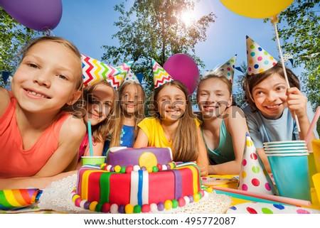 Six happy kids in party hats around birthday cake #495772087