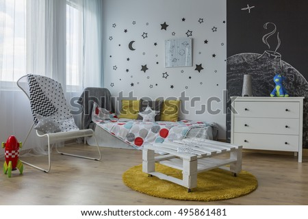 Light and spacious child room with white furniture, blackboard wall and star stickers #495861481