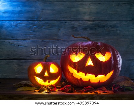Grinning pumpkin lantern or jack-o'-lantern is one of the symbols of Halloween. Halloween attribute. Wooden background. #495897094