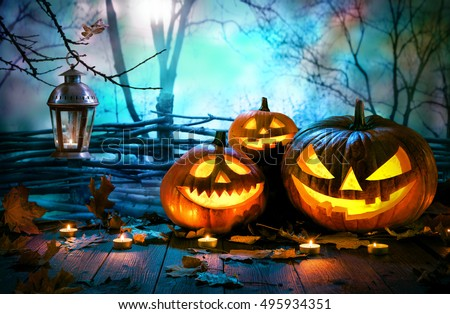 Halloween pumpkins on wood in front of nightly spooky forest background #495934351