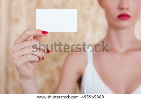 Girl holding empty business card in her hand while standing against beige background. Concept of marketing. Mock up