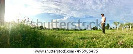 Panorama view of grass field and wind turbines on background #495985495