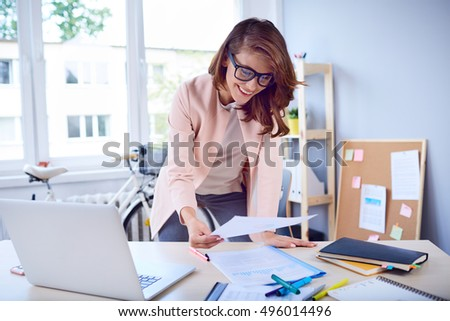 Busy businesswoman working by desk at office #496014496