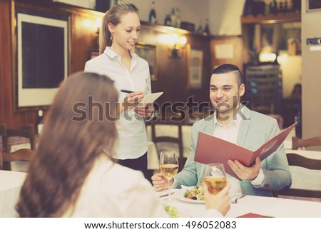 Handsome man with beautiful happy girlfriend making order in cafe #496052083