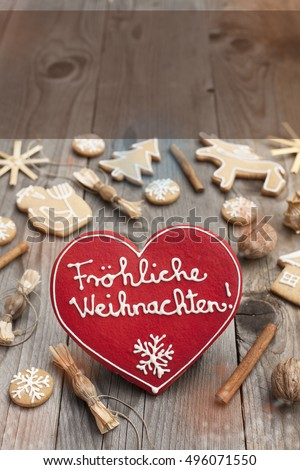 Red Christmas heart shaped gingerbread on wooden background. Space left for copy. Perfect for greeting cards. Merry Christmas written with icing in German #496071550