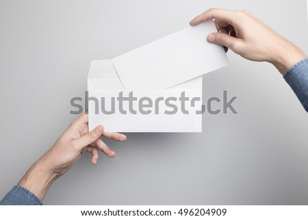 Hand holding Blank Envelope Mock-up, ready to replace your design. Royalty-Free Stock Photo #496204909