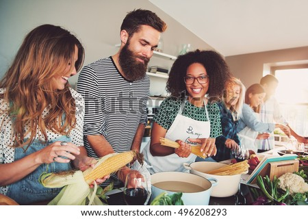 Happy group of young adult men and women cooking together at home in small kitchen or culinary classroom #496208293