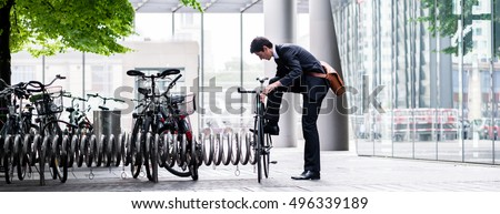 Businessman parking his bicycle in town at a bicycle rack after commuting to work in a concept of eco-friendly transport and healthy active lifestyle, panoramic banner view Royalty-Free Stock Photo #496339189