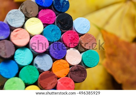 different colored pastel chalks on background of autumn yellow leaves #496385929