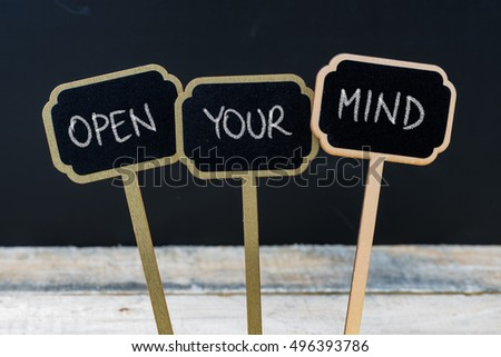 Business message OPEN YOUR MIND written with chalk on wooden mini blackboard labels, defocused chalkboard and wood table in background #496393786