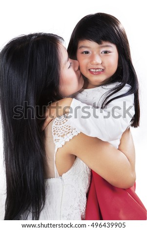 Image of mother giving kiss and hugging her daughter, isolated on the white background #496439905