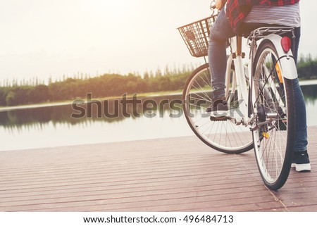 Close-up of young hipster woman holding her foot on bicycle pedal. #496484713