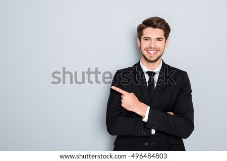 Young handsome businessman with beaming smile pointing with finger #496484803