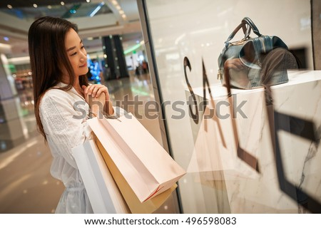 Asian young woman looking at purse in shop window #496598083