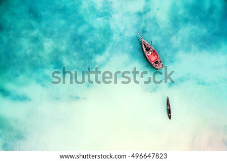 boat and ship in beautiful turquoise ocean near an island, top view, aerial photo #496647823