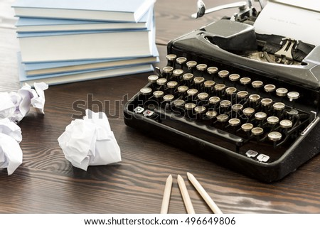 Novelist's desk with the typewriter, books, pencils and creased papers on #496649806