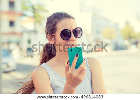 SMS. Closeup portrait funny skeptical, doubtful shocked anxious scared young girl looking at phone seeing bad news photos message with disgusting emotion on face isolated cityscape outdoors background #496814083