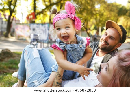 Funny picture of screaming little girl with pink kerchief sitting on mother's belly