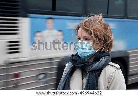 Portrait of woman walking on the street wearing protective mask as protection against infectious diseases.   Royalty-Free Stock Photo #496944622