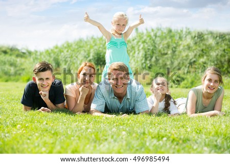 joyful smiling parents with four different age children lying on the grass in park on summer day