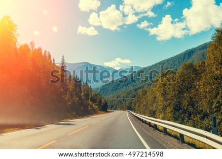Mountain road at sunset with blue cloudy sky #497214598