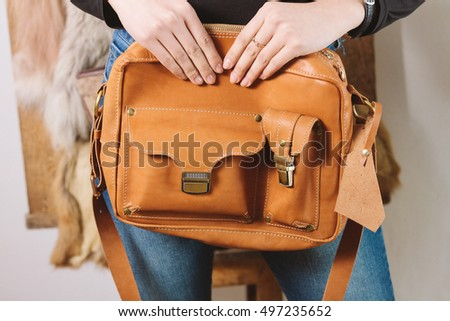 vintage brown leather bag in young woman's hands #497235652
