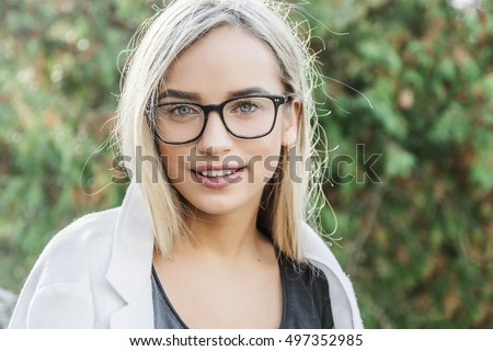 portrait of a young woman, blonde, glasses, outdoors in the park #497352985