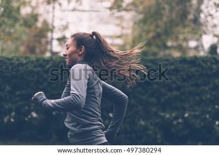 Woman running. Female runner jogging, training for marathon. Fit girl fitness athlete model exercising outdoor. #497380294