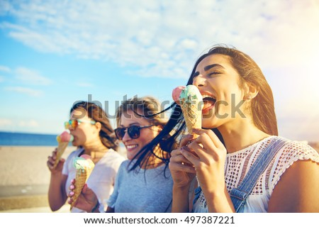 Three young woman eating ice cream cones at the seaside as they stroll along a waterfront promenade on a hot summer day during their vacation #497387221
