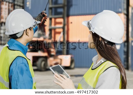 The engineer working with container Cargo freight ship in shipyard at dusk for Logistic Import Export background #497417302