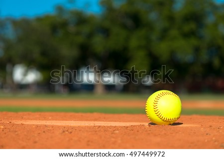 Bright fluorescent neon yellow softball on pitchers mound with field and trees in background