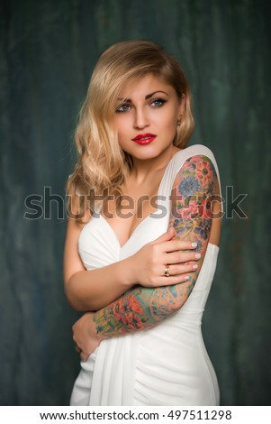 young beautiful blond woman in the white dress. woman with  a tattoo on her shoulder hands, red lipstick, dark background, like Marilyn Monroe, Bride with tattoos
